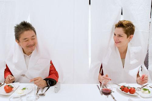 Marije Vogelenzang (rechts) tijdens het door haar ontworpen droog kerstdiner, sharing dinner 2005, waarbij de gasten 'gevangen' in een tafelkleed samen de maaltijd nuttigden. foto: Kenji Masunaga